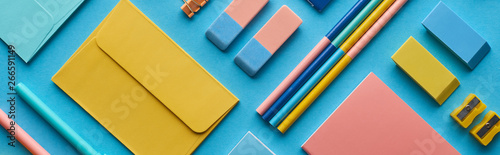 Fotografía panoramic shot of envelope and arranged colorful stationery isolated on blue