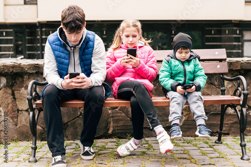 Fotografie, Obraz  Three children sit on a bench and look at the phones, instead of walking, restin