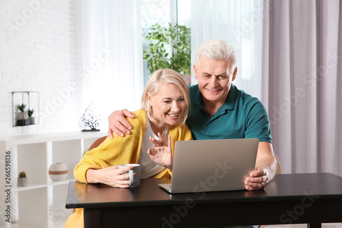 Fotografie, Obraz Mature couple using video chat on laptop at home