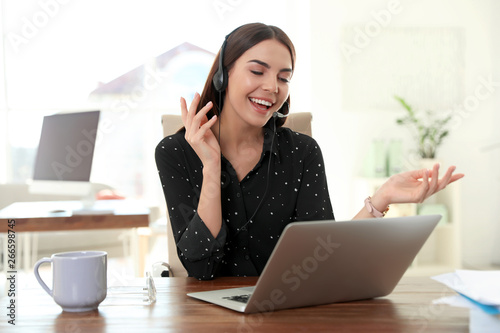 Fotografía Young woman using video chat on laptop in home office
