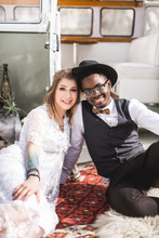 Beautiful Couple African Man In Black Hat And Caucasian Woman In White Dress Smiling And Hugging Each Other While Sitting On Red Carpet On The Sand In Canyon. Retro Minivan On The Background