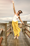 Happy woman moving arms to the wind over the sea - 266606951