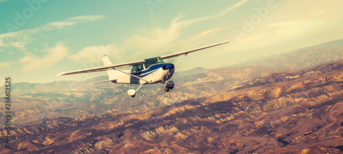 Poster Airplane Small single engine airplane flying in the gorgeous sunset sky through the sea of clouds above the spectacular mountains