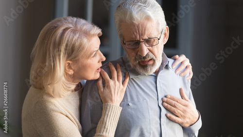 Cuadros en Lienzo Grey haired man touching chest, having heart attack, woman supporting