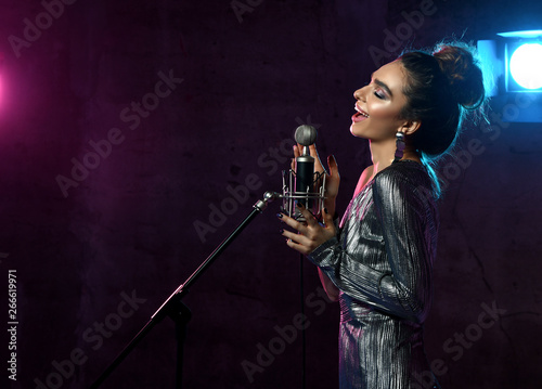 Beautiful singing girl curly afro hair singer sing with microphone karaoke song on stage on dark neon light - 266619971