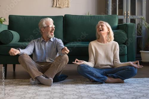 Fotografia  Happy mature couple having fun, practicing yoga together at home