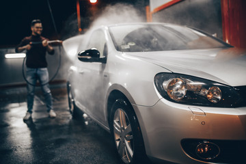 Young man washing his car in the evening at car wash station using high pressure water.