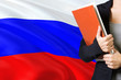 Leinwandbild Motiv Learning Russian language concept. Young woman standing with the Russia flag in the background. Teacher holding books, orange blank book cover.
