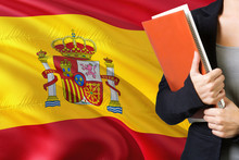 Learning Spanish Language Concept. Young Woman Standing With The Spain Flag In The Background. Teacher Holding Books, Orange Blank Book Cover.