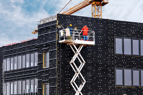 Professional construction workers on scissors mechanism