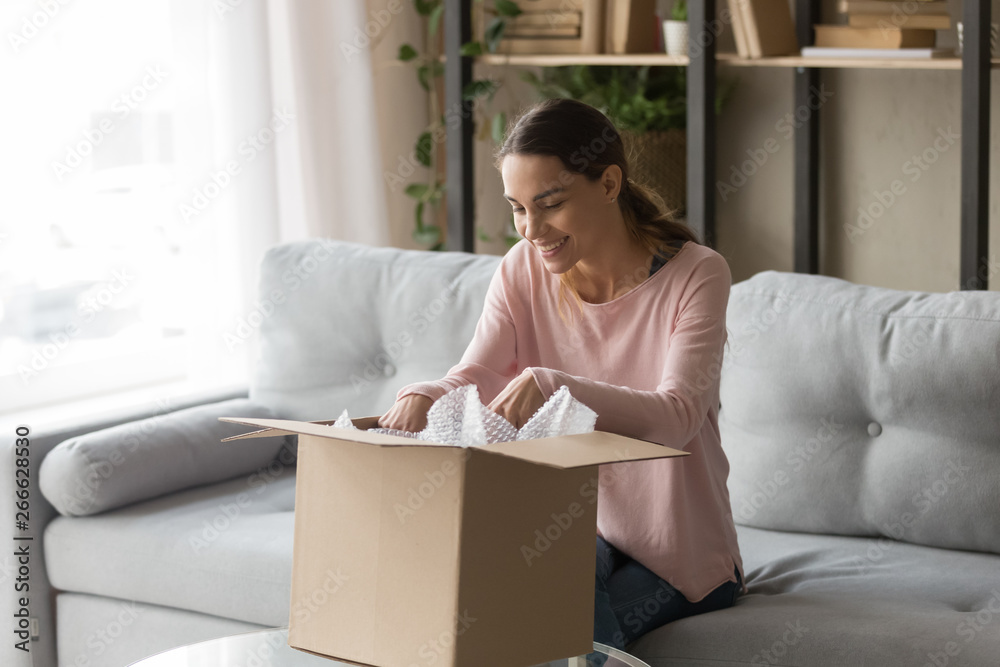 Fototapety, obrazy: Client woman sitting on couch unbox carton box feels satisfied
