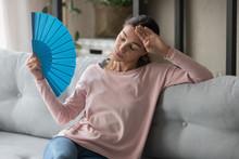 Woman Feels Discomfort From Heat Waving Blue Fan To Cool