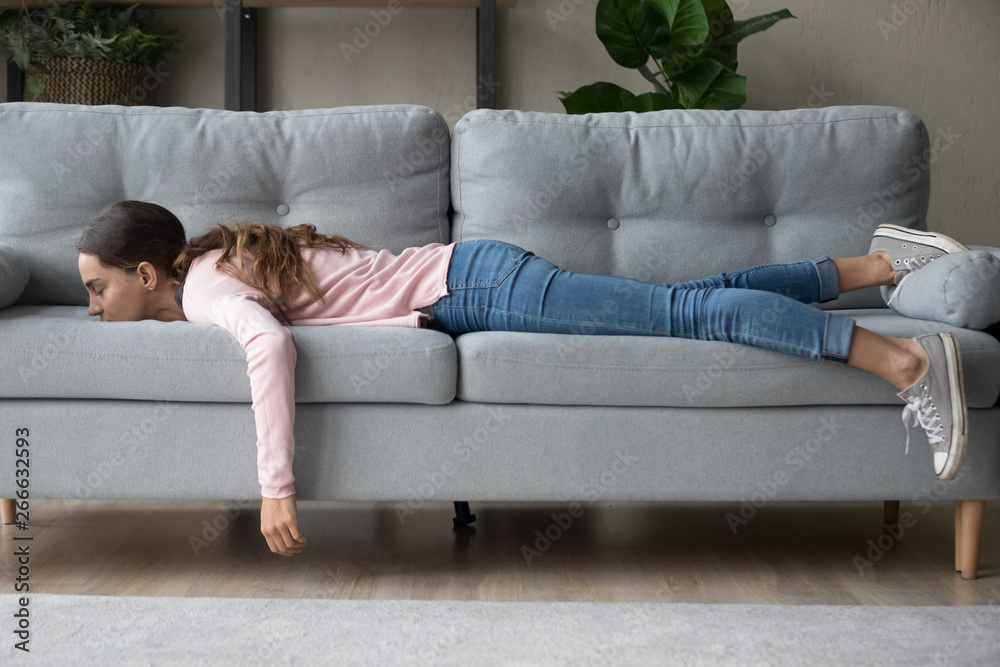 Fototapeta Young woman lying buried her face in sofa feels tired