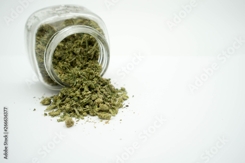 Ground marijuana spilling out of a jar on a white isolated background Wallpaper Mural