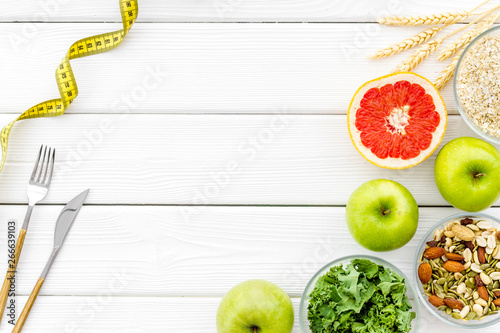 Weight loss concept with oatmeal, nuts, greenery, fruits and measuring tape on white background top view copy space