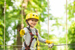 Leinwandbild Motiv Happy child boy calling while climbing high tree and ropes. Portrait of a beautiful kid on a rope park among trees. Small boy enjoy childhood years.