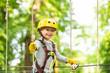 Leinwandbild Motiv Happy child boy calling while climbing high tree and ropes. Portrait of a beautiful kid on a rope park among trees. Small boy enjoy childhood years.