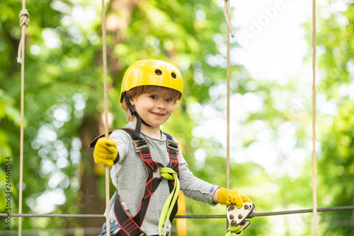 Fototapety, obrazy: Happy child boy calling while climbing high tree and ropes. Portrait of a beautiful kid on a rope park among trees. Small boy enjoy childhood years.