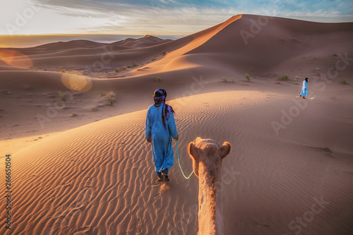 Fotobehang Cappuccino Two Tuareg nomads dressed in traditional long blue robes, lead a camel through the dunes of the Sahara Desert at sunrise in Morocco.