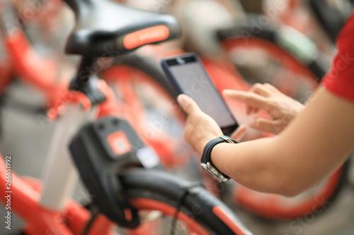 Valokuva  Hands using smartphone scanning the QR code of shared bike in city