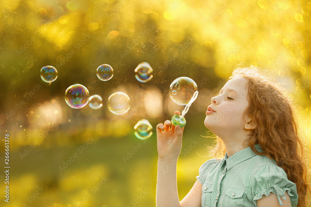 Fototapety, obrazy: Little girl blowing soap bubbles in spring outdoors.