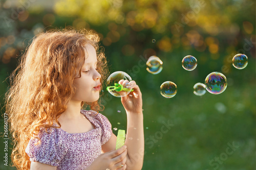 Poster Artist KB Little girl blowing soap bubbles in spring outdoors.