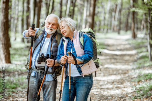 Aluminium Prints Personal Beautiful senior couple hiking with backpacks and trekking sticks in the forest. Concept of active lifestyle on retirement