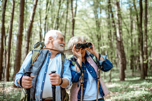 Beautiful senior couple hiking with backpacks and trekking sticks in the forest. Concept of active lifestyle on retirement