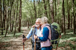 canvas print picture - Lovely senior couple hugging in the forest while hiking with backpacks and trekking sticks. Concept of active lifestyle on retirement