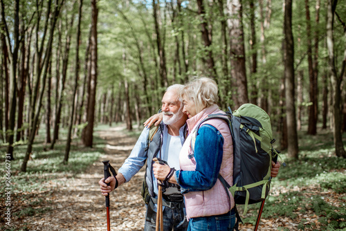 Fotografía  Lovely senior couple hugging in the forest while hiking with backpacks and trekking sticks