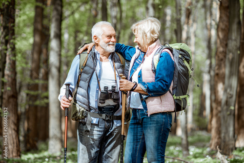 Obraz Lovely senior couple hugging in the forest while hiking with backpacks and trekking sticks. Concept of active lifestyle on retirement - fototapety do salonu