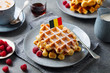 canvas print picture - Waffles with icing sugar and Belgium flag on a plate. Grey background.