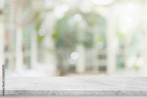 obraz lub plakat Empty white stone marble table top and blurred of interior room with window view green from tree garden background background - can used for display or montage your products.