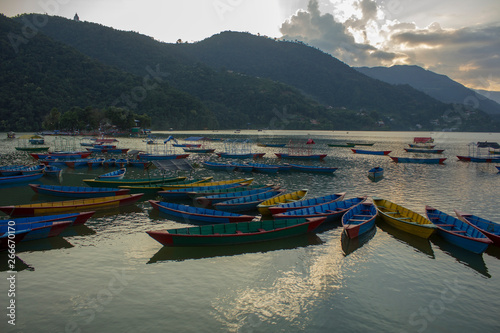 Foto op Canvas Nepal wooden old empty colorful boats on the lake Phewa on the background of a mountain valley in the fog and the evening sky