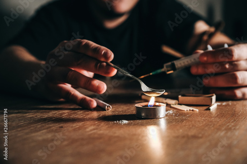 Fotografija  Man preparing heroin on fire