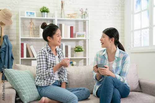 Fotografie, Obraz two happy young asian female friends with coffee cups conversing in living room at home