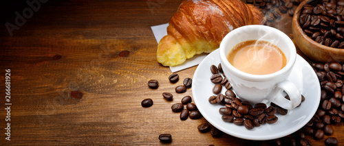 Leinwand Poster Espresso and croissant with coffee beans on wood background