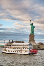 The Statue Of Liberty In New York City With Ferry Boat