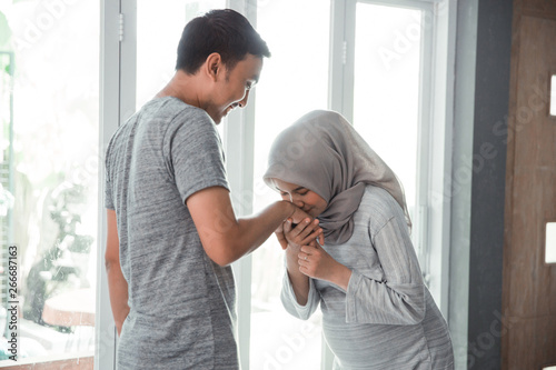 Photo muslim woman shake hand and kiss her husband's hand at home