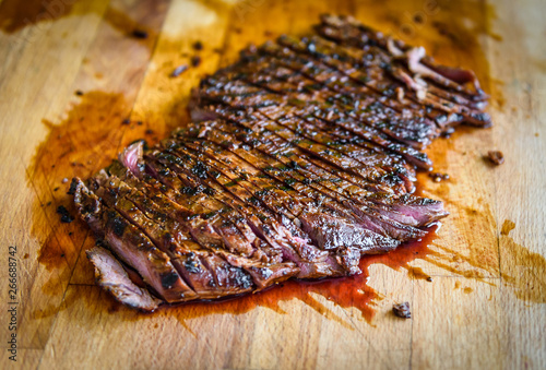 Fotomural Sliced grilled juicy marinated beef flank steak on wooden board.