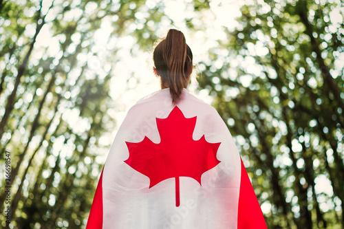 Slika na platnu Child teenager girl at nature background an Canada flag on her shoulders