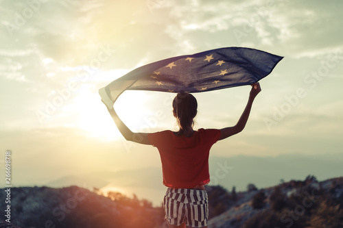 Child girl teenager young person is waving European Union flag on top of mountain at sky background. Sunset time