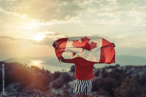 In de dag Canada Happy child teenage girl waving the flag of Canada while running at sunset