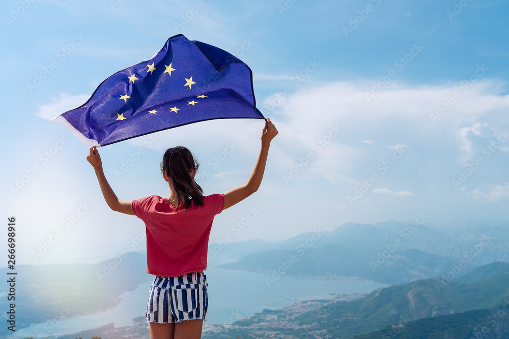 Fototapety, obrazy: Child girl teenager young person is waving European Union flag on top of mountain at sky background