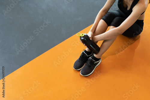 Fotografia  Woman exercise workout in gym fitness breaking relax holding protein shake bottl