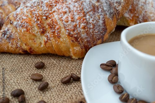 Wall Murals Cafe Croissants and coffee with cinnamon on a wooden Board. Hardwood worktop as a background.