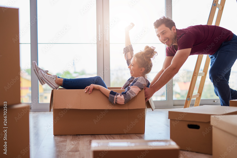 Fototapety, obrazy: Playful couple having fun with boxes during move house