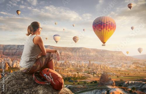 Obraz na plátně  Happy woman traveler watching the hot air balloons at the hill of Cappadocia, Turkey
