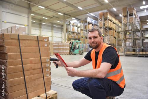 Lagerarbeiter scannt Pakete im Lager einer Spedition für den Transport // Warehouse worker scans parcels in the warehouse of a forwarding company for transport