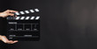 canvas print picture - Hand is holding Black clap board or movie slate  use in video production , movie ,film, cinema industry on black background.It have write in number.